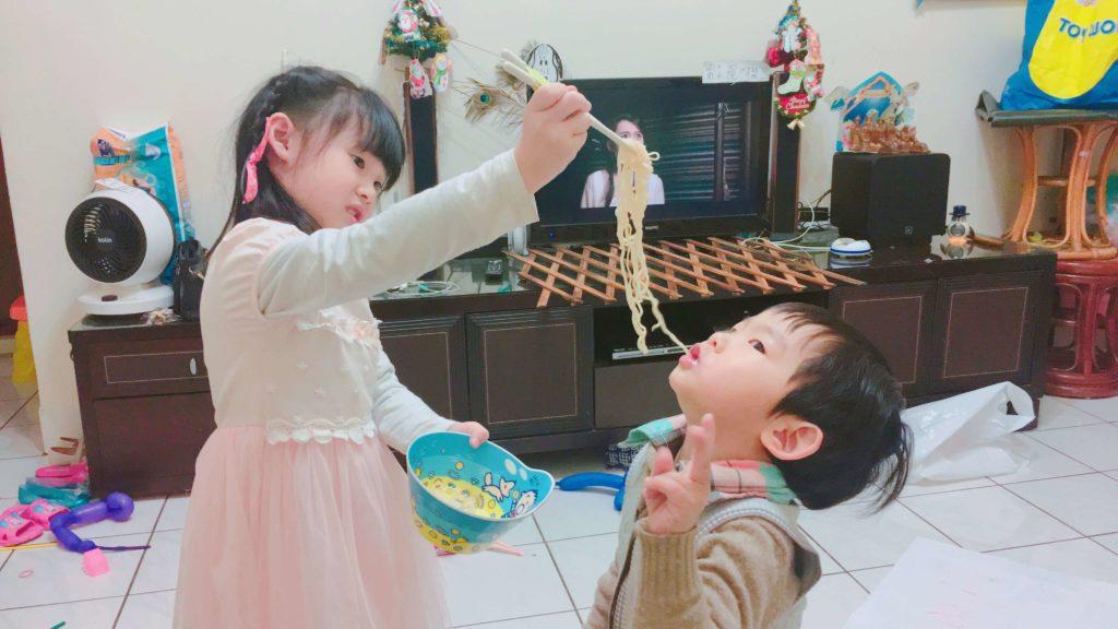 姊姊用筷子餵弟弟吃麵